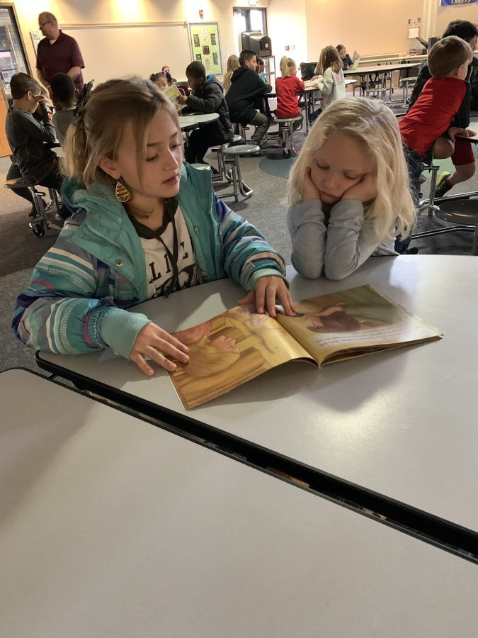 Young students working together to read a book aloud